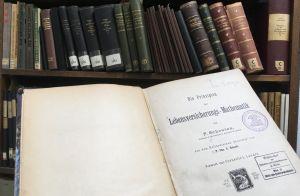 """""""Die Prinzipien der Lebensversicherung-Mathematik"""" vor den Bänden der historischen Bibliothek der Handels-Hochschule Berlin"""